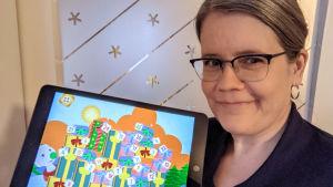 Pia Manns håller i en pekplatta med BUU-klubbens applikation.