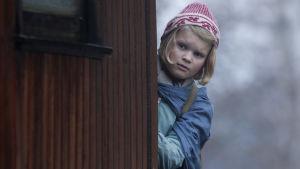 Gerda (Anna Sofie Skarholt) kikar fram bakom ett hörn.