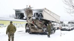 En pansarvagn transporterar en förflyttbar bro i ett snölandskap. På bilden syns också soldater.