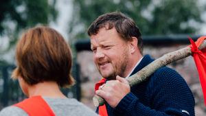 Micke Björklund pratar med Maria Sundblom Lindberg som har ryggen mot kameran. Micke håller i en käpp med en röd flagga på.