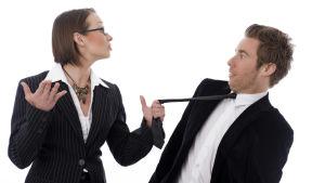 Nainen kiskoo miehen solmiosta.