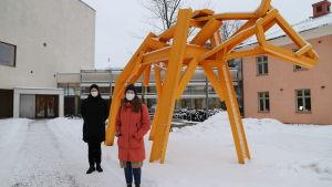 Andrea Södergård och Minna Hemgård står bredvid ett konstverk som föreställer en gul ko på Åbo stadsbiblioteks innergård.