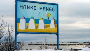 Hangö-skylt vid en strand. På skylten finns fyra ritade badhytter, sol, strand, blå himmel och texten Hanko-Hangö.