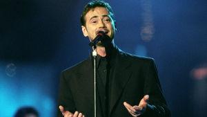 Christer Björkman sjunger i en mikrofon iklädd svart kostym år 1992