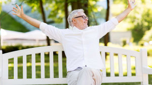 Leende äldre man sitter på bänk och slår ut med armarna