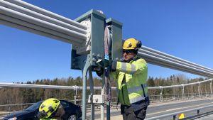 Två män iförda arbetskläder byter ut ett hängstag på Rävsundsbron en solig dag.