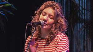 Kvinna med långt, lockigt hår och randig tröja sjunger i mikrofon.