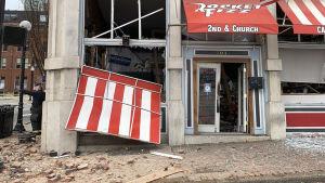 Bild på förstörd byggnad med rödvitrandiga markiser.
