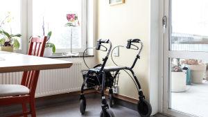 Lägenhet med köksbord, stol, rollator och balkongsdörr.
