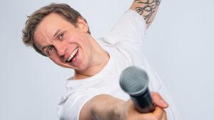 Hymyilevä Konsta Hietanen mikrofoni kädessään