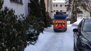 Juuso Sahlberg kör en maskin för att sanda en trottoar i Borgå