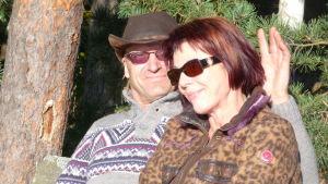 en man och en kvinna sitter på en bänk i solsken, okober, de ser lyckliga ut