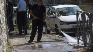 En kommunalarbetare tvättar gatan i Jerusalem där den palestinska tonåringen sköts ihjäl under lördagsmorgonen.