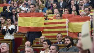Spanska flaggan lyfts fram efter omröstning i det katalanska parlamentet.