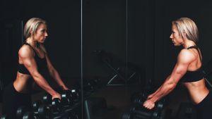 kvinna i konditionssal ser sin muskulösa kropp i spegeln