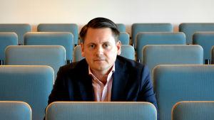 Markus Norrgård, ansvarig professor för Helsingfors universitets juridiska fakultet i Vasa, sitter mitt i ett auditorium och ser rakt in i kameran.