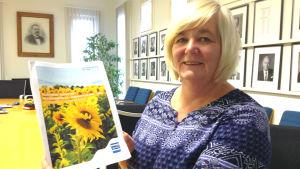 En kvinna som heter Benita Öberg håller i Sjundeå kommuns budgetförslag. På pärmen är solrosor.