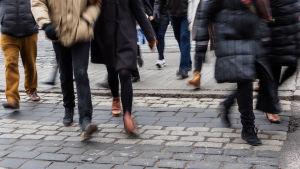 Jalankulkijoita suojatiellä. Anonyymi ihmisiä kiire