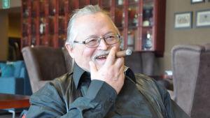 Illustratören Hannu Lukkarinen med en cigarr i munnen