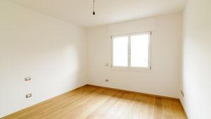 Ett tomt rum med fönster, vita väggar och parkettgolv.