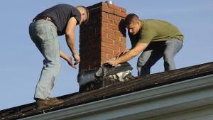 Två män reparerar en skorsten med jesustejp efter en jordbävning i Virginia i USA i augusti 2011.