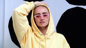 Den svenska hiphop-artisten Silvana Imam sitter med ena handen bakom huvudet, hon har på sig glasögon och en gul munkjacka.