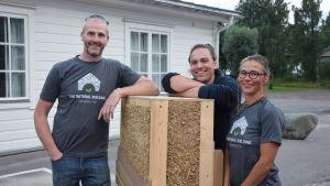 tre personer står kring en modell för en vägg. bakom dem ett hus och träd.