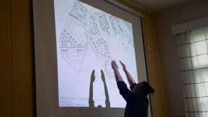 En man pekar på en stor skärm ut det område som ska bli bostadsområde