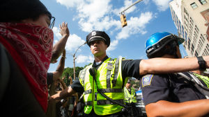 En polis försöker hålla motdemonstranterna borta.