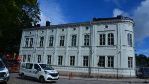 vitt gammalt stenhus i två våningar invid Domkyrkan och Åbo akademis huvudbibliotek. Vi paketbil i förgrunden