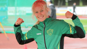 Emilia Karell firar guldmedaljen med att lyfta upp händerna.