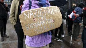 """En demonstrant med en skylt med texten """"Nazit = Pahaa on kiistämätön yhtälö""""."""