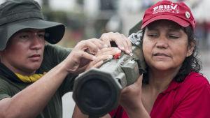 En kvinna håller i ett vapen på sin axel medan en man hjälper till i Caracas den 26 augusti. Både militära och civila deltog i Venezuelas militärövning.