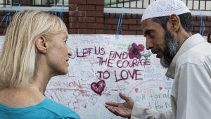 En kvinna och en muslimsk man diskuterar framför en skylt som uppmanar till kärlek och samverkan.