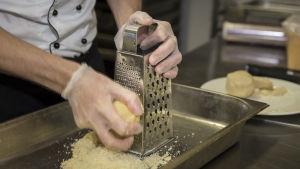 En kock river ost i ett stort metallkärl.