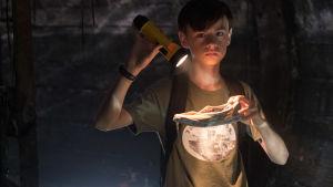 Bill i avloppstunnel med ficklampa i handen.