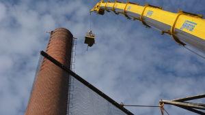 En bur hissas upp med en lyftkran upp mot toppen av en gammal skorsten av tegel.