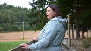 Maria Damén står vid porten till en fårhage.