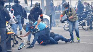 Kravallpolis griper en demonstrant i staden Nantes under en demonstration mot nya arbetsmarknadslagar.