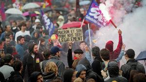 """Tusentals demonstrerade i Paris mot arbetsreformen. """"Macron och hans värld dödar oss lagligt,"""" står det på skylten."""