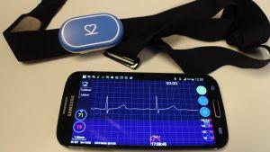 Elektrokardriogram-apparat samt EKG-kurva på en mobilskärm