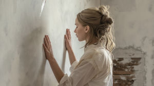 Hon med händerna på väggen.