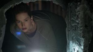 Hon närmar sig nyfiket en mystisk tunnel i källaren.