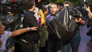 En man bär ett paket som tros innehålla en valurna, till en av vallokalerna i Barcelona.