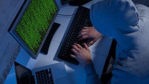 Person iklädd munkjacka sitter vid en laptop och en dator med en massa gröna tecken på skärmen.
