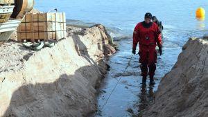 Sjökabel dras in i ett dike av en man vid stranden.