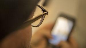 Kännykkää katsotaan sillmälasien kanssa.