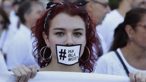 """En ung flicka bär en mask med texten """"ska vi tala?"""""""
