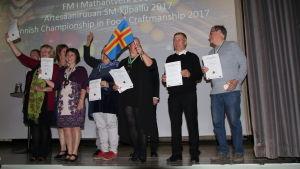 Flera personer står på en scen efter att de fått medaljer i mattävlingen Mathantverk.