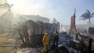 Brandmän vid ett nedbrunnet hus i Anaheim Hills, Kalifornien.